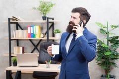 咖啡是成功的交涉承诺  使上瘾的咖啡因 人有胡子的商人举行杯子和智能手机 ?? 免版税库存照片