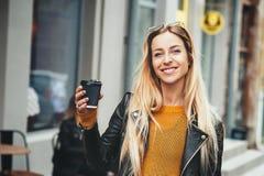 咖啡是 微笑美丽的年轻白肤金发的妇女拿着咖啡杯和,当走沿街道时 库存图片