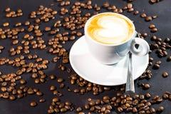咖啡晚杯子和豆在黑背景 免版税库存图片