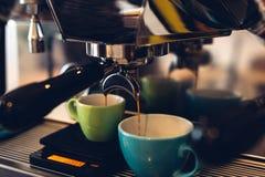 咖啡机器倾吐的咖啡到一个两个色的杯子里 库存图片