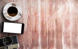 咖啡杯、巧妙的电话和老照相机在木桌上 库存照片