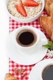 咖啡杯、新月形面包、燕麦粥用草莓和小树枝  库存照片