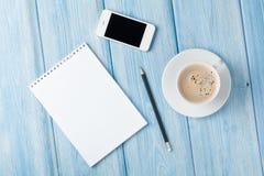 咖啡杯、智能手机和空白的笔记薄在木桌bac 免版税库存图片