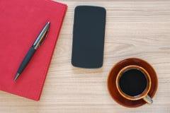 咖啡杯、智能手机和笔记本在木书桌上 免版税库存照片