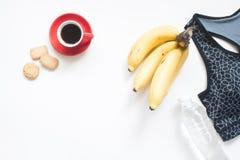 咖啡杯、曲奇饼、香蕉、水和体育胸罩顶视图在whi 免版税库存照片