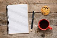 咖啡杯、曲奇饼和笔记本有笔的 图库摄影