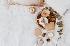 咖啡杯、曲奇饼和金装饰在床上 甜家,静物画概念 图库摄影