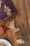 咖啡杯、秋叶和日志在木桌上 免版税库存图片