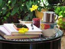 咖啡杯、笔记本、铅笔和花在绿色钢桌上做它你自己 角落放松概念 图库摄影