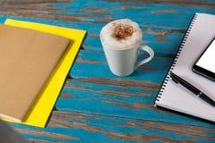 咖啡杯、笔记薄、智能手机、笔和日志 库存照片