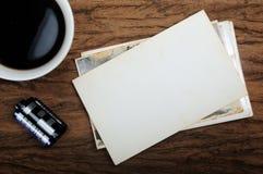 咖啡杯、老纸照片框架和照相机影片在木backgr 图库摄影