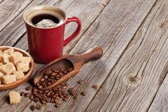 咖啡杯、豆和红糖在木桌上 免版税图库摄影