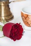 咖啡杯、铜罐和红色玫瑰 免版税库存照片
