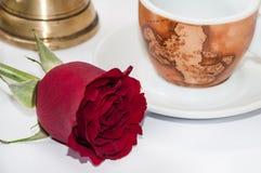 咖啡杯、铜罐和红色玫瑰 免版税库存图片