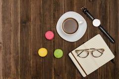 咖啡杯、macarons、手表、笔记本和玻璃在一张木桌上 侧视图 免版税库存图片