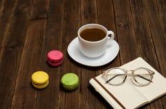 咖啡杯、macarons、笔记本和玻璃在一张木桌上 侧视图 库存图片