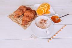 咖啡杯与在白色土气桌上的新月形面包、果酱、桔子和笔记早晨好从上面,舒适和鲜美早餐,葡萄酒 库存图片
