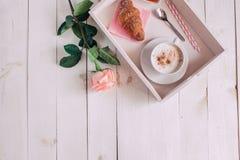 咖啡杯与在白色土气桌上的新月形面包、玫瑰、果酱和笔记早晨好从上面,舒适和鲜美早餐,葡萄酒 库存照片