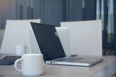 咖啡杯与labtop计算机的热奶咖啡在桌上在办公室 免版税库存照片