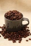 咖啡杯充满在粗麻布的豆 免版税库存照片