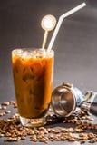 咖啡杯凉快的冰和豆在黑背景 免版税图库摄影