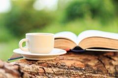 咖啡杯和书在木头 免版税库存图片