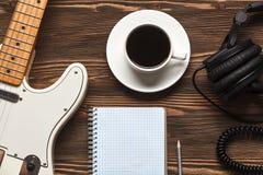 咖啡杯和吉他在木桌上 库存图片