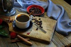 咖啡杯和咖啡豆在木桌上 免版税库存图片