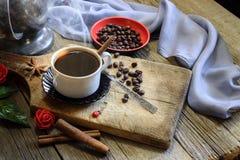 咖啡杯和咖啡豆在木桌上 免版税图库摄影
