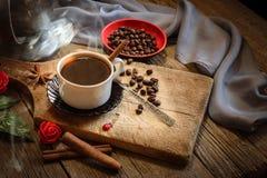 咖啡杯和咖啡豆在木桌上 免版税库存照片