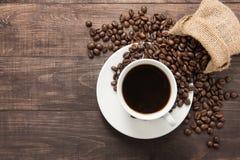 咖啡杯和咖啡豆在木背景 顶视图 免版税库存图片