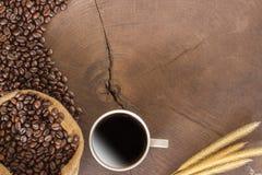 咖啡杯和咖啡豆在木头 免版税库存图片
