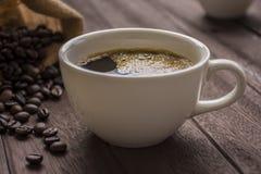 咖啡杯和咖啡豆在桌上 免版税库存图片