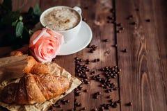 咖啡杯和咖啡豆,在棕色木桌上的新月形面包 库存照片