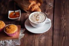 咖啡杯和咖啡豆,新月形面包,蛋糕,在棕色木桌上的橙色果酱 图库摄影