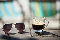 咖啡杯和太阳镜在木桌上与海滩睡椅&沙子 库存照片