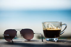 咖啡杯和太阳镜在木桌上与海滩睡椅&沙子 免版税库存图片