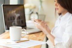 咖啡杯和女实业家与文件和膝上型计算机一起使用 免版税库存照片
