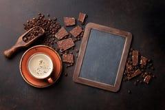 咖啡杯和巧克力在老厨房用桌上 库存照片
