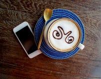 咖啡杯和巧妙的电话在老木桌上 图库摄影