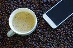 咖啡杯和巧妙的电话用咖啡豆 免版税库存图片