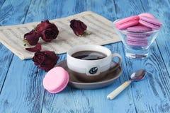 咖啡杯和干红色玫瑰在木桌上 库存照片