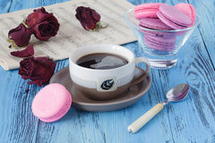 咖啡杯和干红色玫瑰在木桌上 库存图片