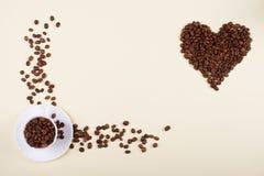 咖啡杯和心脏由疏散豆做成 免版税库存照片