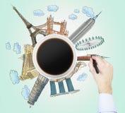 咖啡杯和手的顶视图在世界上画最著名的城市的五颜六色的剪影 旅行的概念 免版税图库摄影