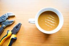 咖啡杯和技工工具 免版税库存照片