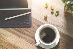 咖啡杯和数字式桌靠码头巧妙的键盘,花瓶开花她 免版税库存图片