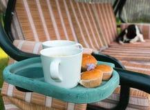 咖啡杯和杯形蛋糕在持有人在庭院摇摆 库存图片