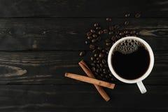 咖啡杯和桂香在黑木头 库存照片