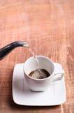 咖啡杯和热水在一张木桌上 库存图片